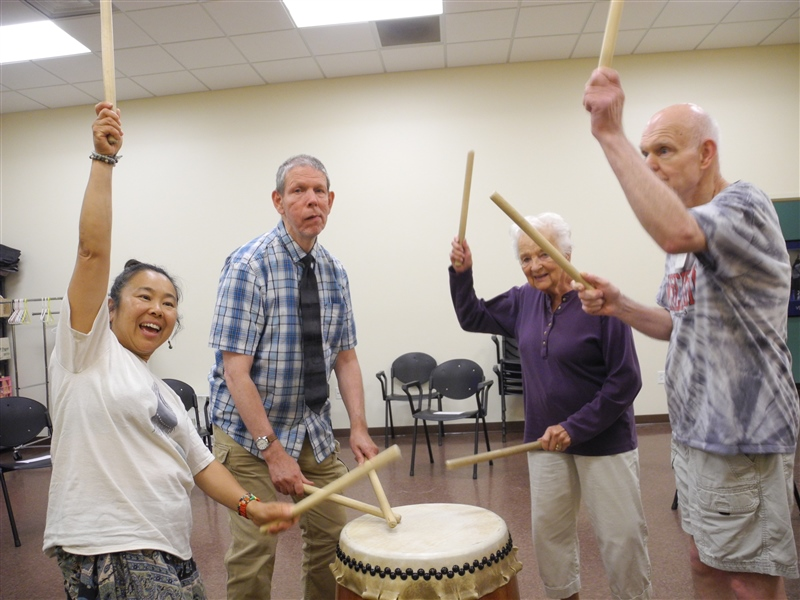 Four people stand around a large drum with drumsticks in their hands